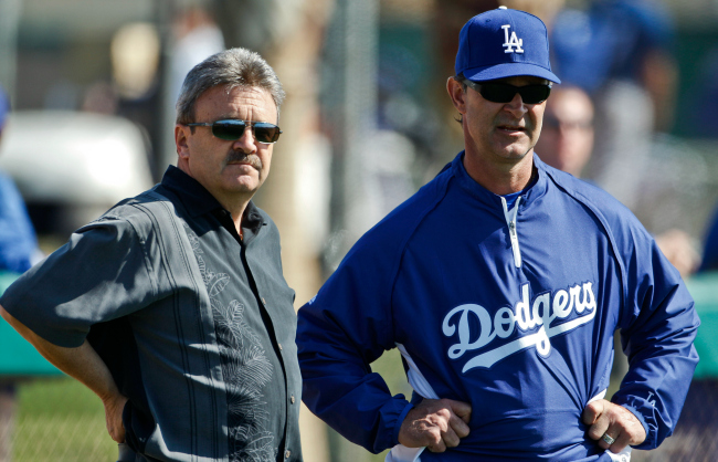 Los Angeles Dodgers manager Don Mattingly talks to general manager Ned Colletti during a spring training baseball workout Wednesday, Feb. 23, 2011, in Glendale, Ariz. (AP Photo/Morry Gash)